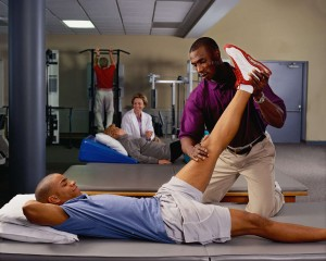 A physical therapist helps a patient with his leg